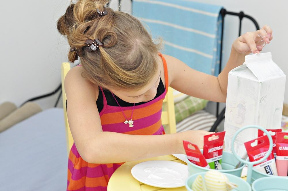 dziecko pokazuje jak zrobić karmnik dla ptakow