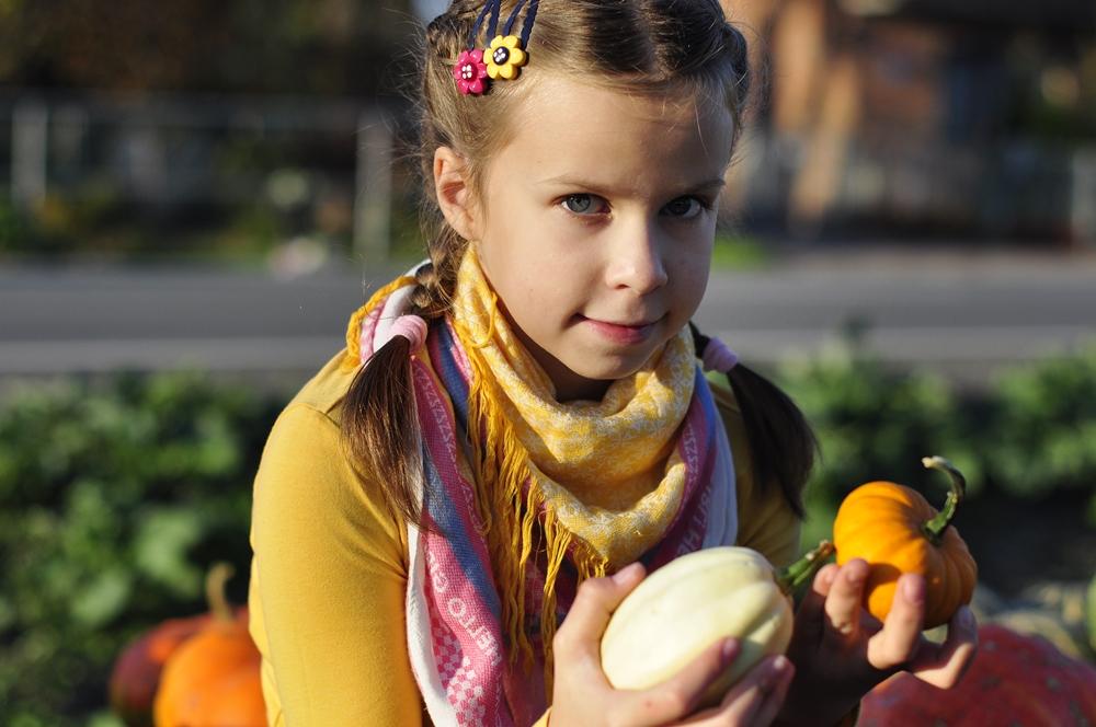 dziewczynka trzymająca dynie w rękach