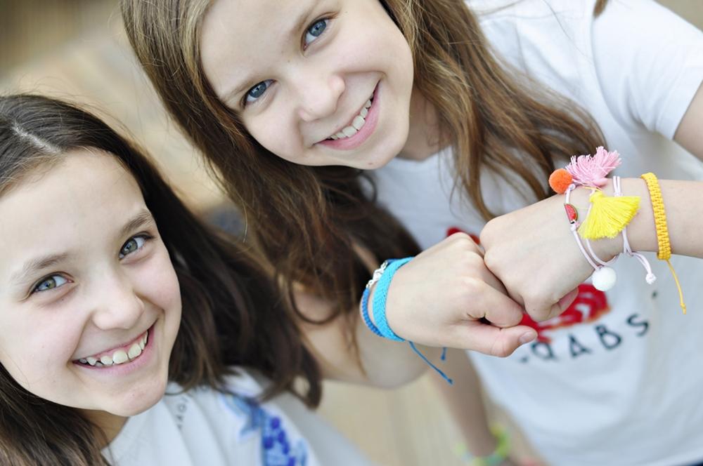 uśmiechnięte dzieci pokazują swoje bransoletki przyjaźni