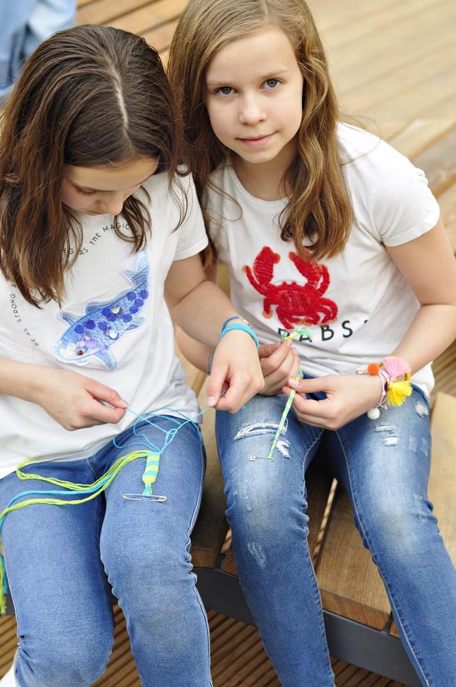 jedna dziewczynka robi bransoletkę przyjażni druga spogląda do przodu