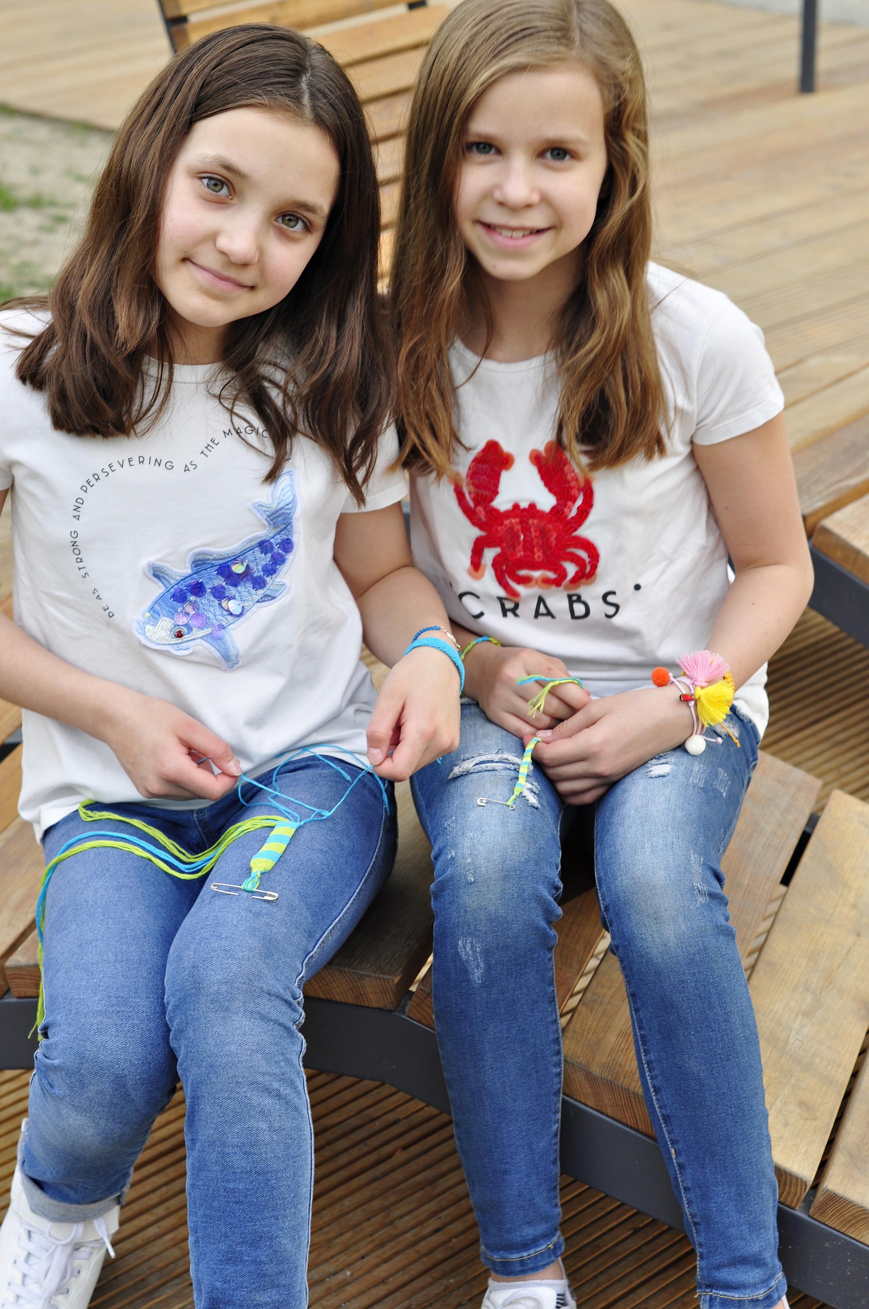 dziewczynki siedzą na ławce i pokazują jak zrobić bransoletkę z muliny