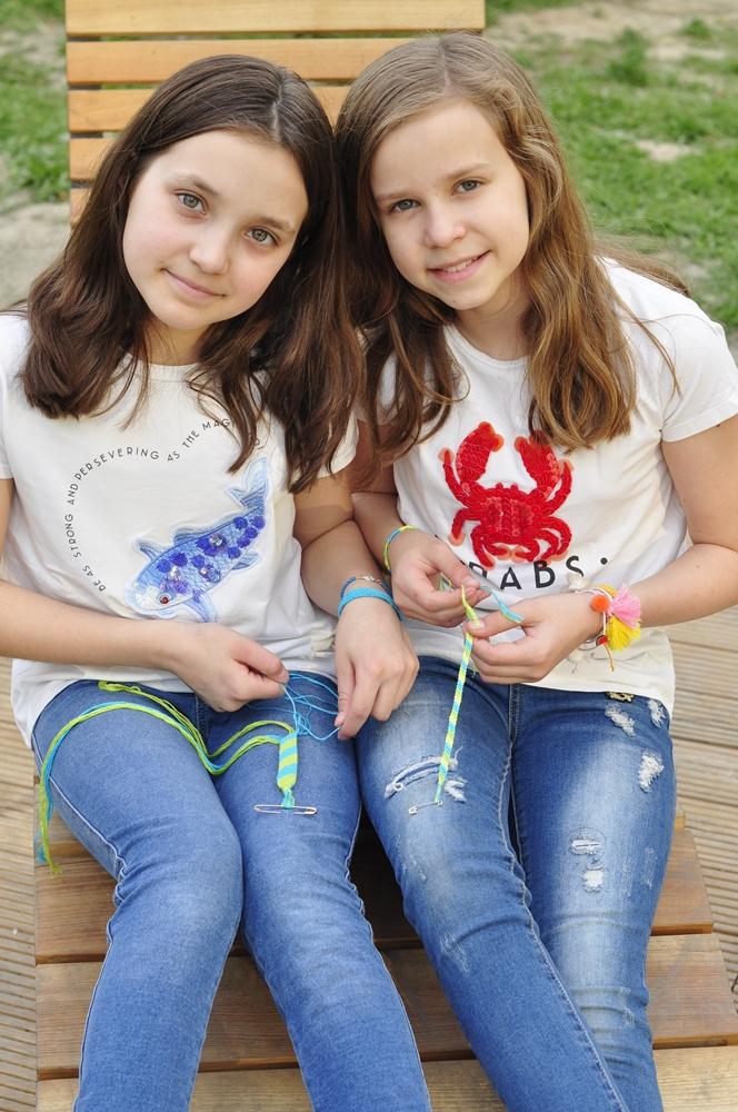 wesołe dziewczynki siedzą na ławce w parku i robią bransoletki przyjaźni