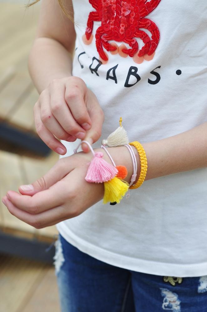 zbliżenie dłoni dziecka ozdobionej kolorowymi bransoletkami ze sznurka