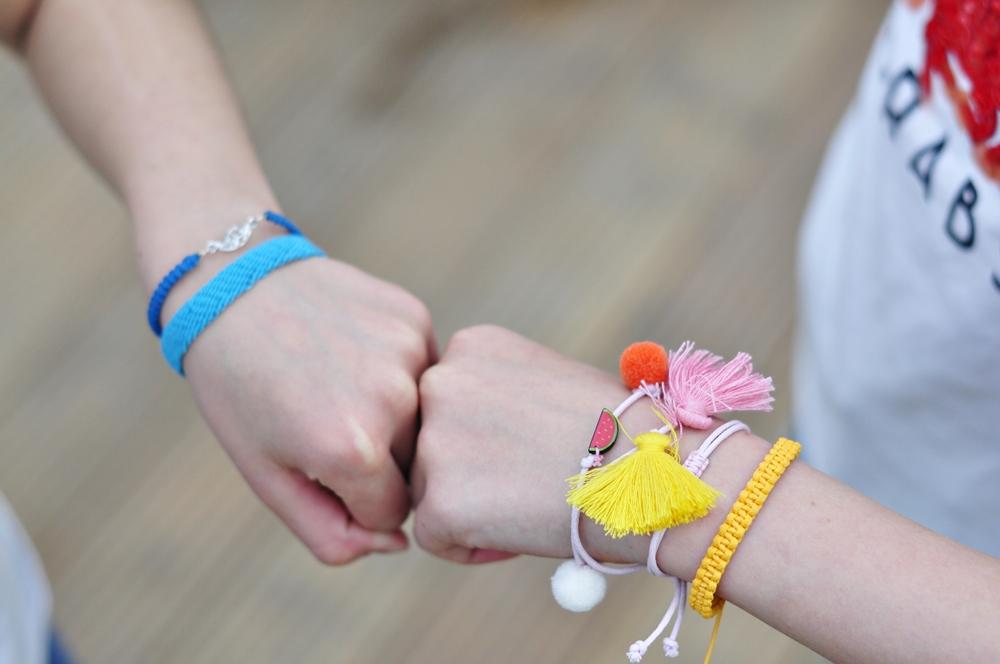 dziewczynki robią źółwika dłońmi ozdobionymi bransoletkami ze sznurka