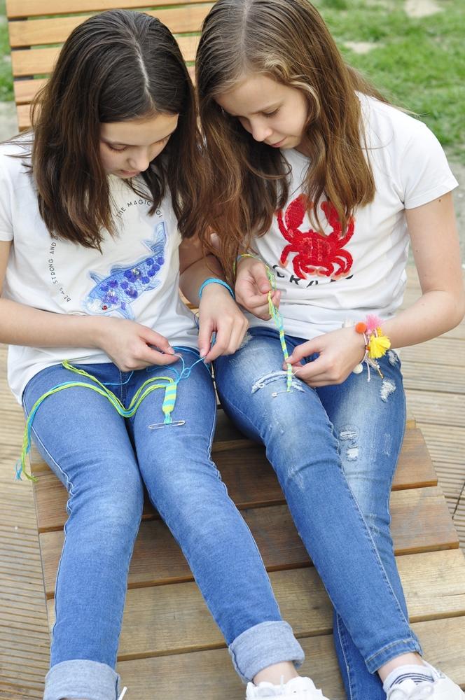 dziewczynki siedzą blisko siebie i każda robi swoją bransoletkę z muliny