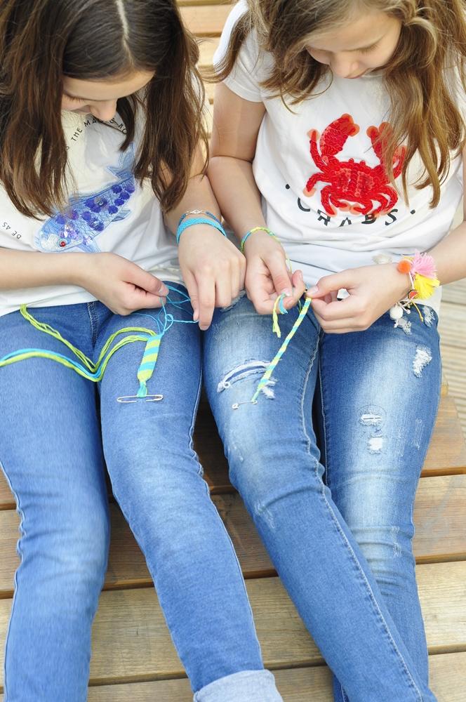 dwie dziewczynki mają pochylone głowy i patrzą na zaplatane przez nie bransoletki ze sznurka