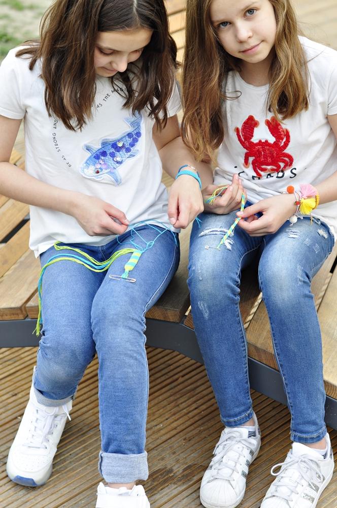 jedna dziewczynka pokazuje jak zrobić bransoletki przyjażni, druga patrzy do przodu