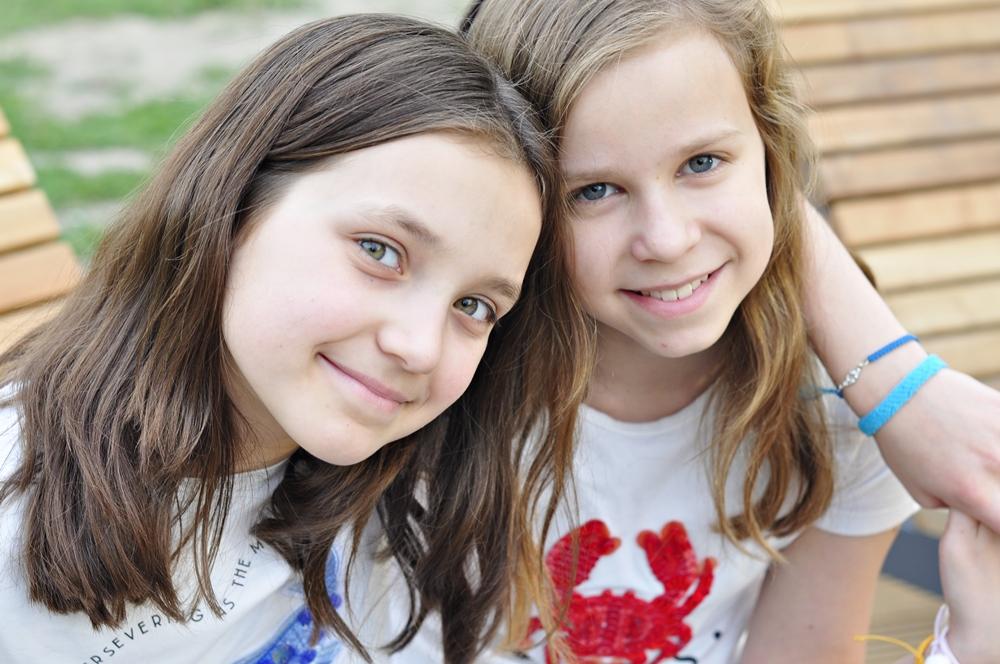 dwie koleżanki siedzą na ławce w parku, na ręce jednej z nich widać bransoletkę