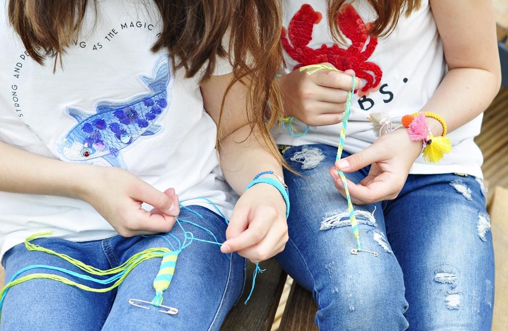 dłonie dwóch dziewczynek zaplatają bransoletki przyjaźni przyczepione do spodni
