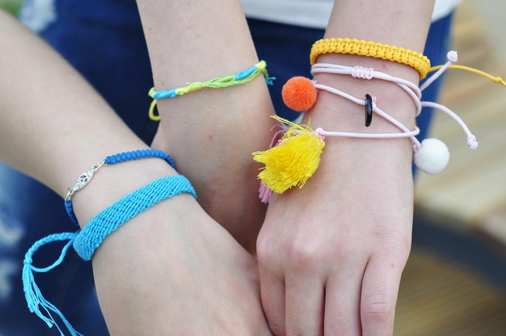 zbliżenie rąk na których są kolorowe bransoleki zrobione z muliny
