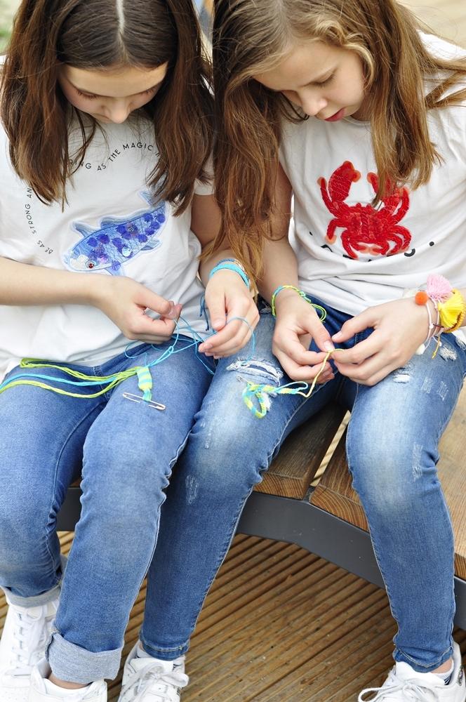 dłonie dwóch dziewczynek zaplatających kolorowe bransoletki przyjaźni