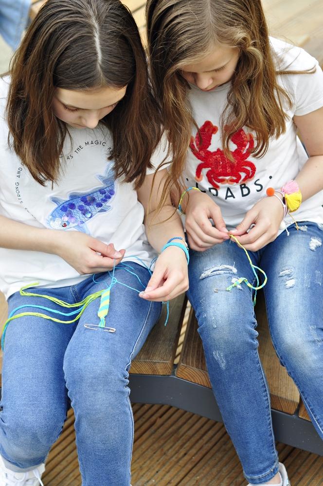 dwie dziewczynki skupione na zaplataniu bransoletek z muliny