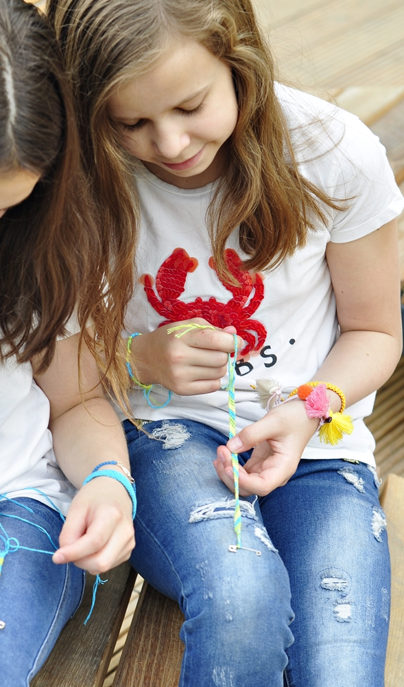 dziewczynka zaplata z muliny bransoletkę dla przyjaciółki