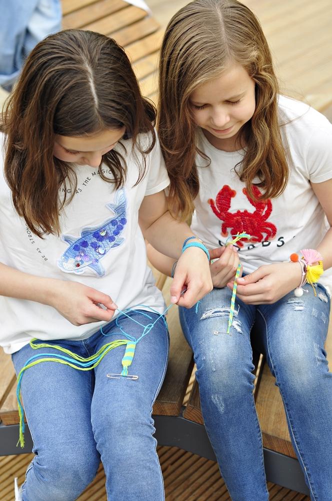 dwie dziewczynki patrzą w dół na zrobione przez siebie bransoletki z muliny