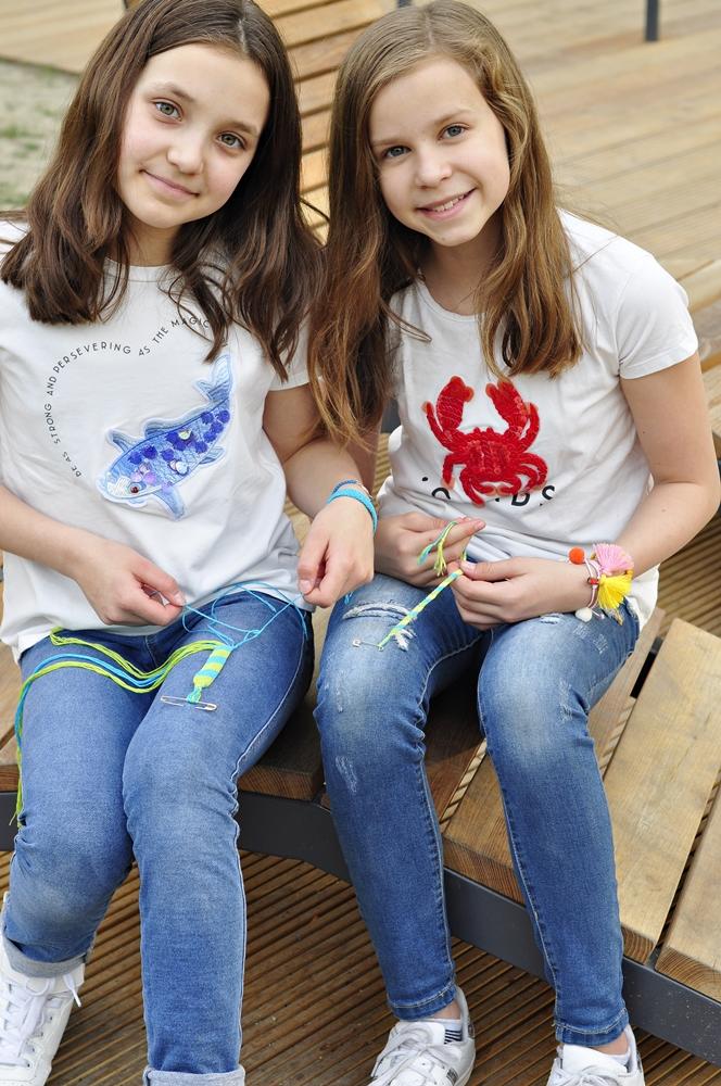 dwie dziewczynki kolorowo ubrane robią w parku na ławce bransoletki przyjażni