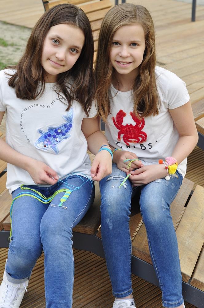 dwie dziewczynki pokazują jak samemu zrobić bransoletkę z muliny