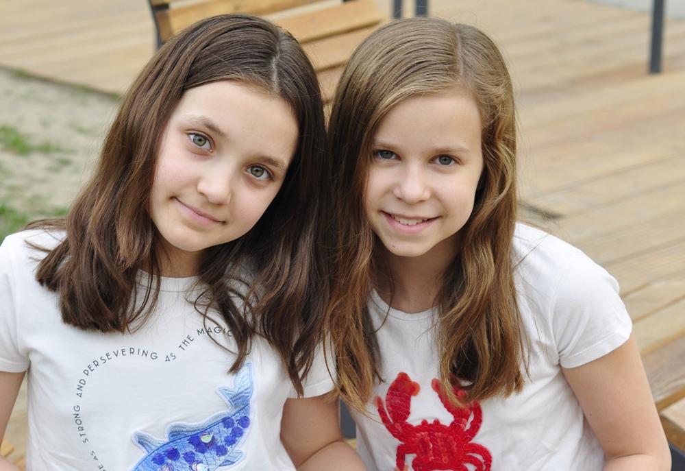 wesołe dziewczynki siedzą na ławce w parku