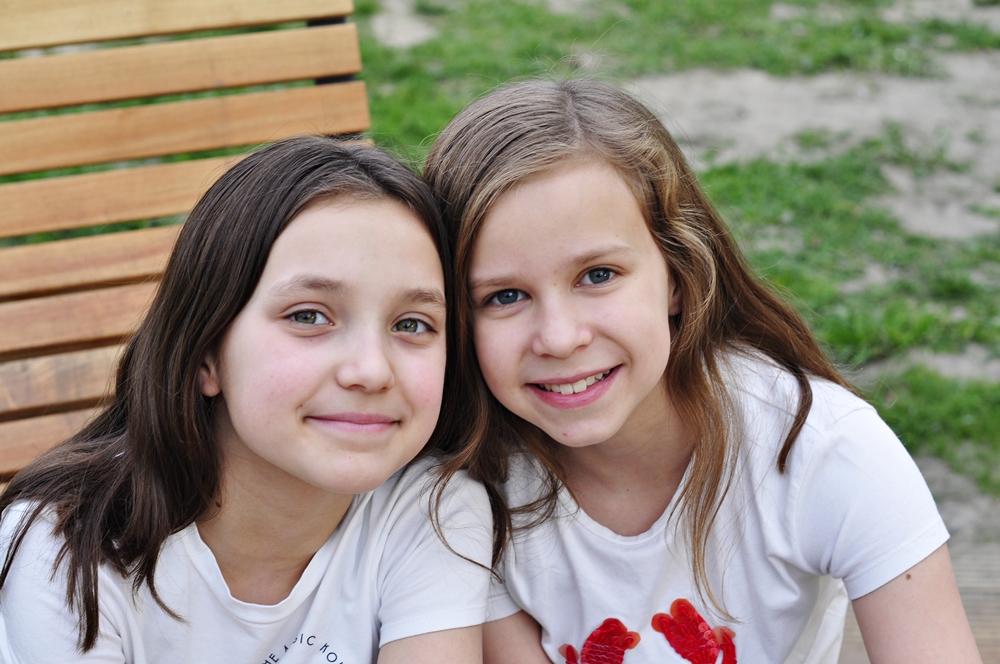 uśmiechnięte dziewczynki siedzą na ławce w parku