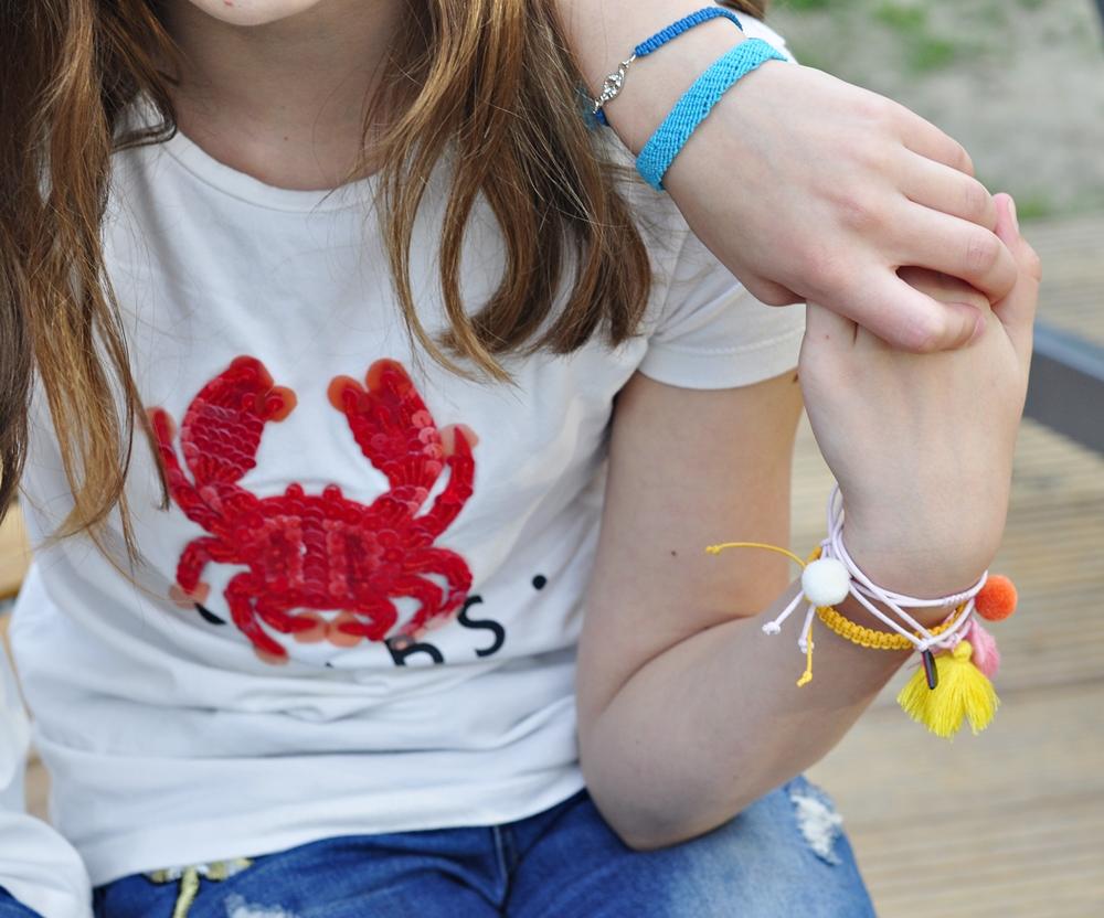 ozdobione bransoletkami dłonie dwóch przyjaciółek splecione razem